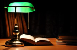 green table lamp and opened book
